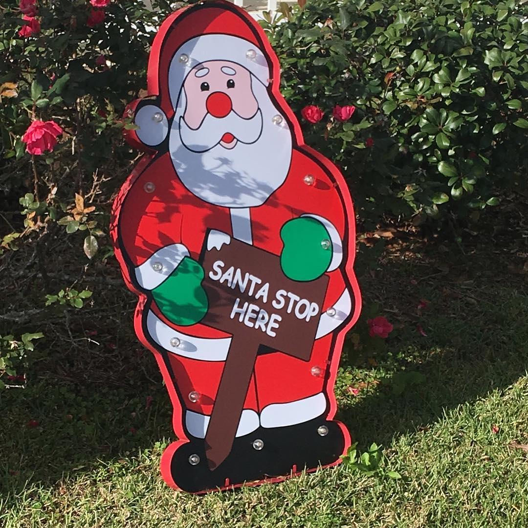 santa holding sign that asks santa to stop here
