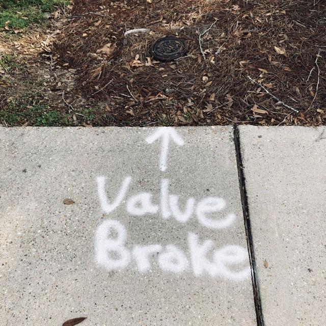 "utilities co. spray painted on sidewalk, reading ""Valve Broke"""