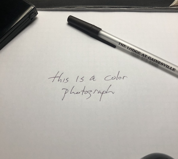 black ink on white paper reading 'this is a color photograph'