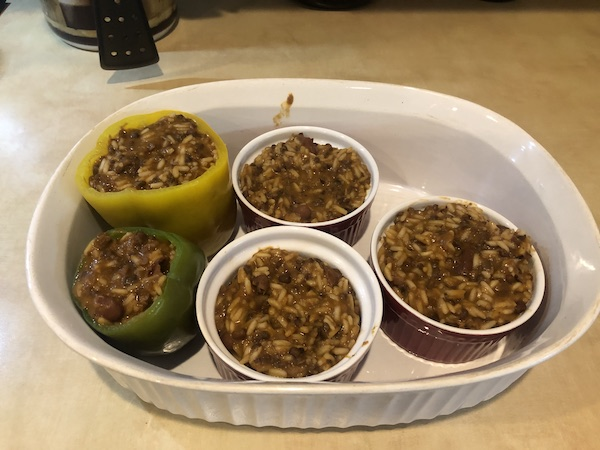 big serving dish with 2 small bell peppers and 3 big ramekins, all full of lentil chili